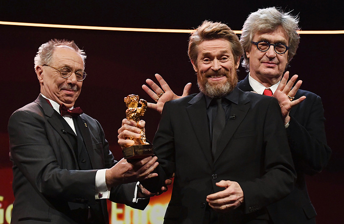 US actor Willem Dafoe smiles as he receives the Golden Bear award from festival director Dieter Kosslick and director Wim Wenders during the Hommage Willem Dafoe - Honorary Golden Bear award ceremony at the 68th annual Berlin International Film Festival, in Berlin, Germany, February 20