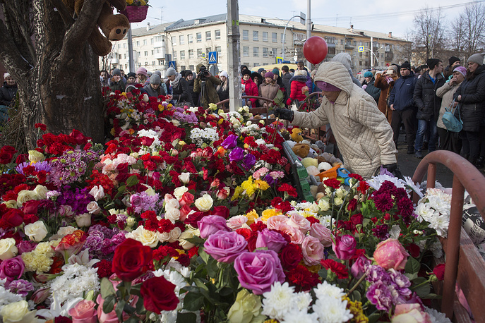 People lay flowers for the victims of a fire at  Zimnyaya Vishnya shopping center in Kemerovo