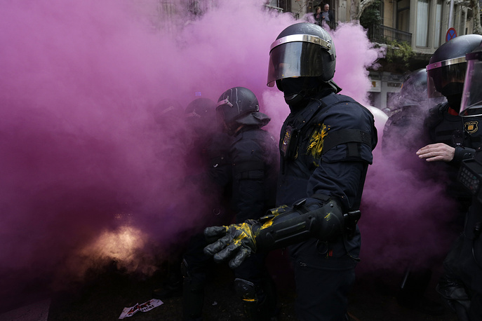 Catalan Mossos d'Esquadra regional police officers stand amid smoke from a smoke bomb during clashes with pro-independence supporters trying to reach the Spanish government office in Barcelona, Spain, March 25