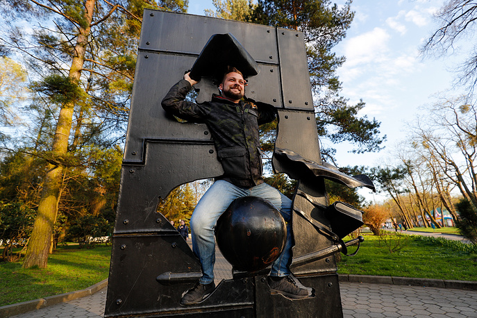 A man poses for a photograph by a monument to Baron Munchausen in Kaliningrad
