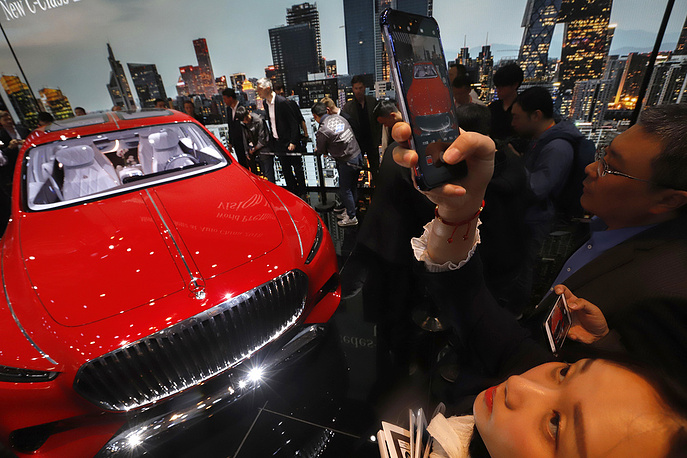A women takes a photo of the Mercedes-Maybach Vision displayed at the Auto China 2018 show held in Beijing
