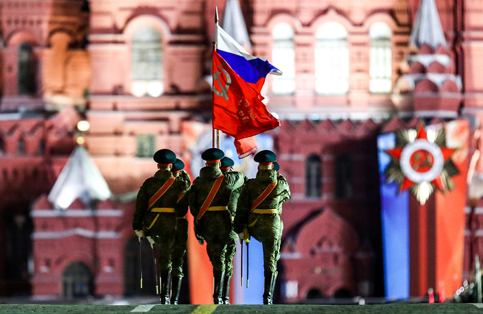 Russian servicemen carry a Russian national flag and the Victory Banner