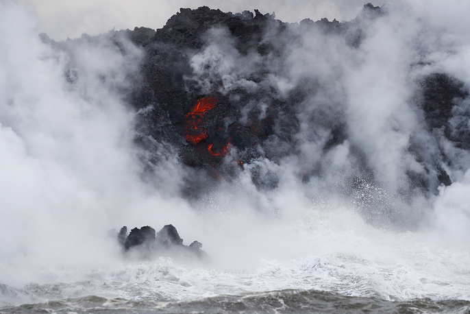 Steam rising as lava flows into the ocean near Pahoa, Hawaii