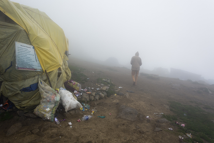 A man walks past a shop with overflowing garbage bags at a popular tourist hiking destination in Dharmsala, India. Each year more visitors walk the mountain trails, putting pressure on local resources such as water and producing a huge amount of plastic waste