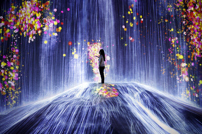 A young woman stands in a digital artwork on display at the digital art museum 'teamLab Borderless' by Japanese creative group teamLab in Tokyo, June 11