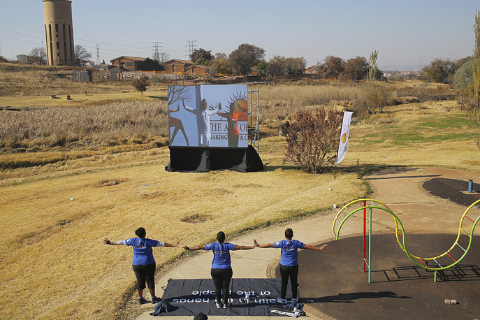Three women practice yoga while watching a huge screen with yogi instructors leading a class at an outside venue as part of World Yoga Day in Soweto Johannesburg, South Africa