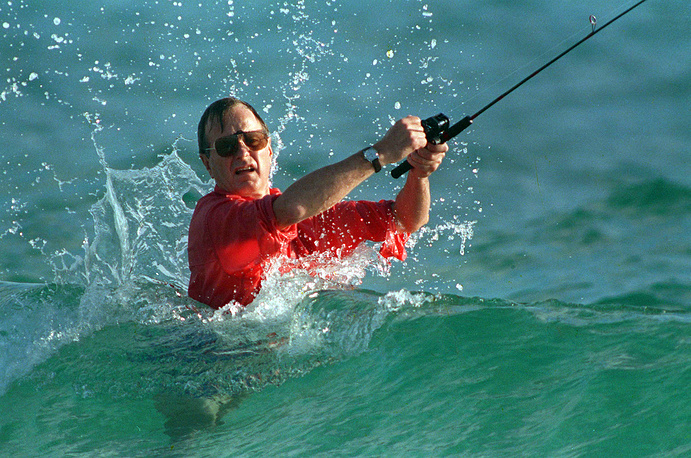 Waves splash former US president George Bush as he casts a line while surf-fishing in Gulf Stream, 1988