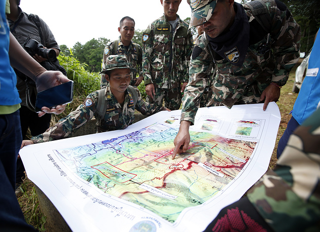 Thai forest rangers examine a map during the ongoing rescue operations for the child football team and their assistant coach, at a mountain forest near Tham Luang cave in Khun Nam Nang Non Forest Park, Thailand