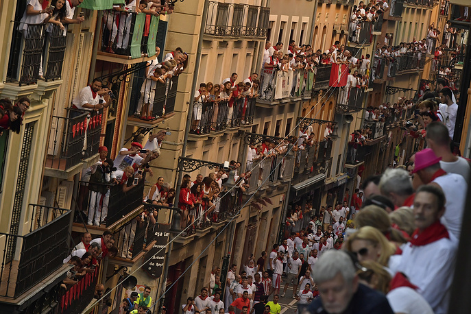People on balconies wait for the start on the running of the bulls at in Pamplona