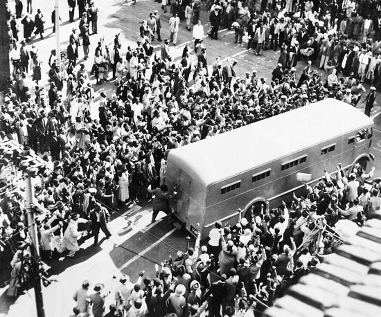 Nelson Mandela was a South African anti-apartheid revolutionary, political leader, and philanthropist who served as President of South Africa from 1994 to 1999. Photo: Crowds cheer as a police van brings prisoners to the Drill Hall, in Johannesburg, South Africa, 1956, for the start of the 'Treason Trial'. Nelson Mandela was among the people arrested and standing trial