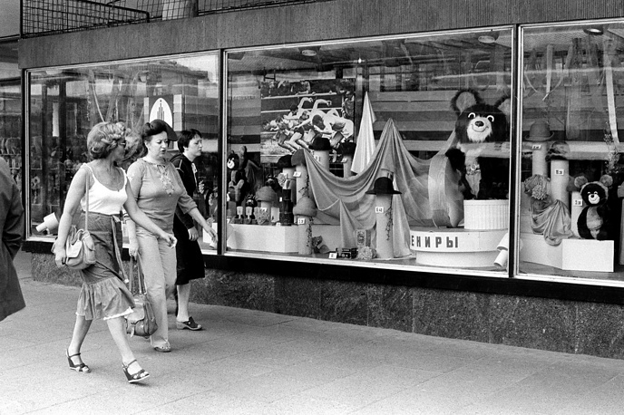 Shoppers walk past a store window displaying Misha the Bear Cub, the 1980 Moscow Olympic mascot, and other Olympic souvenirs in Moscow, June 16, 1980