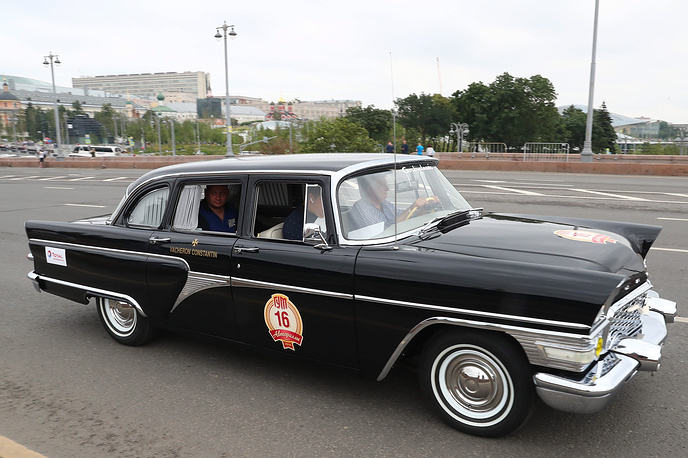 GAZ Chaika car on Bolshoi Moskvoretsky Bridge during the start of the 2018 GUM Gorkyclassic Motor Rally featuring classic cars.