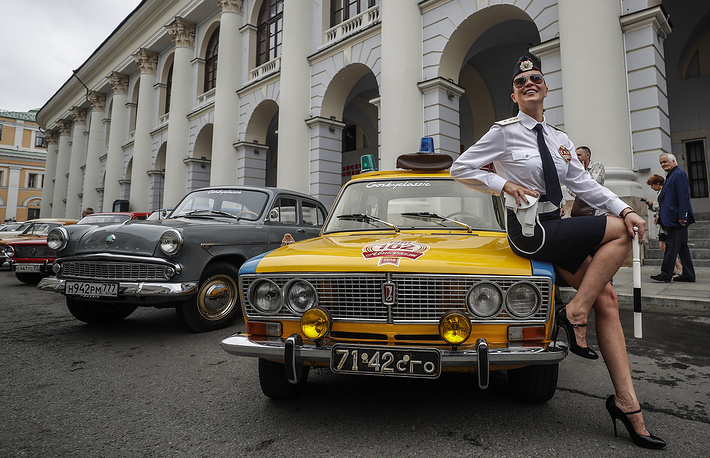 A girl in the uniform of employees of the State traffic police sits on a 'Zhiguli' VAZ-2103 GAI