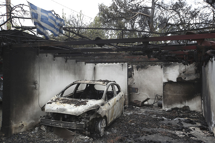 A Greek national flag fluttering over the charred remains of a burned-out car and house in Mati east of Athens