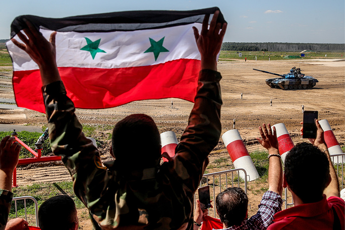 Syrian military officers support their team during an individual race in Stage 1 of the Tank Biathlon Contest