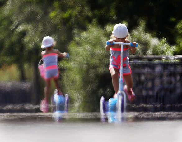 Two little girls ride their scooters through the shimmering heat on the tarmac of a former military airport in Frankfurt, Germany