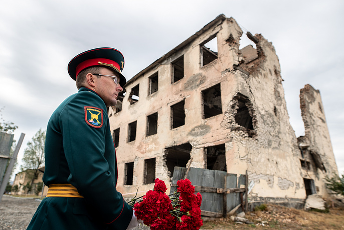 A Russian serviceman during a flower laying ceremony at the Memorial cross installed by a building in the Shanghai residential neighborhood of the city of Tskhinval where the Russian peacekeeping forces used to be stationed ahead of the 2008 Georgia-South Ossetia military conflict