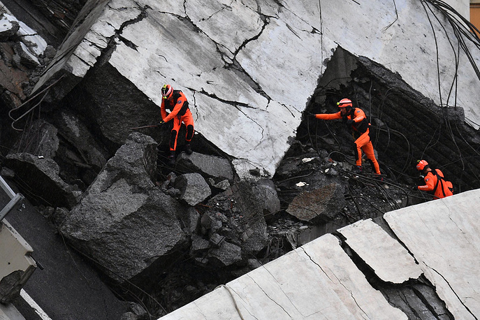 Rescuers at work amid the rubble after a highway bridge collapsed in Genoa
