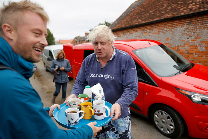 Britain's former Foreign Secretary Boris Johnson offers cups of tea to journalists outside his home near Thame in Oxfordshire, August 12