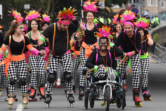 A dance troupe arrive to perform on roller blades during the Notting Hill Carnival Family Day