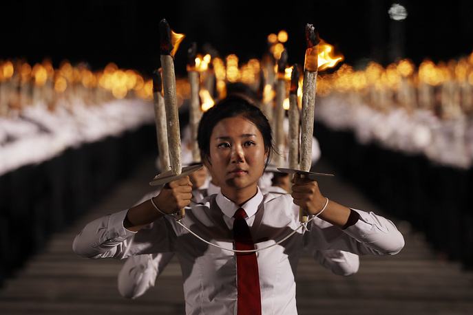 North Korean youths holding torches march at the Kim Il Sung Square
