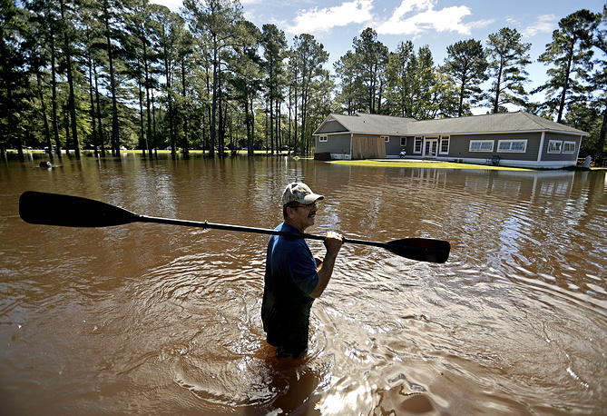 The building is surrounded by water as local citizen retrieves a paddle that floated away in Linden, North Carolina