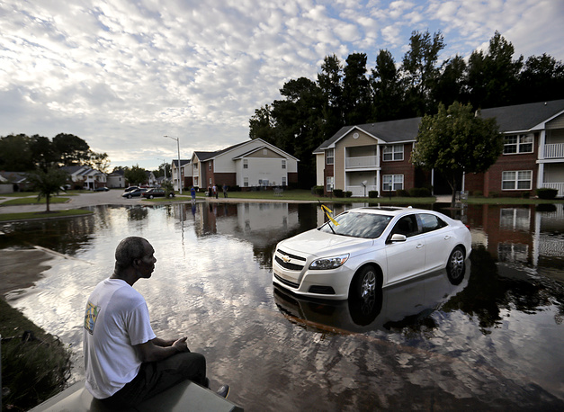 A man looks out at the flooded entrance to his apartment complex near the Cape Fear River in Fayetteville, North Carolina