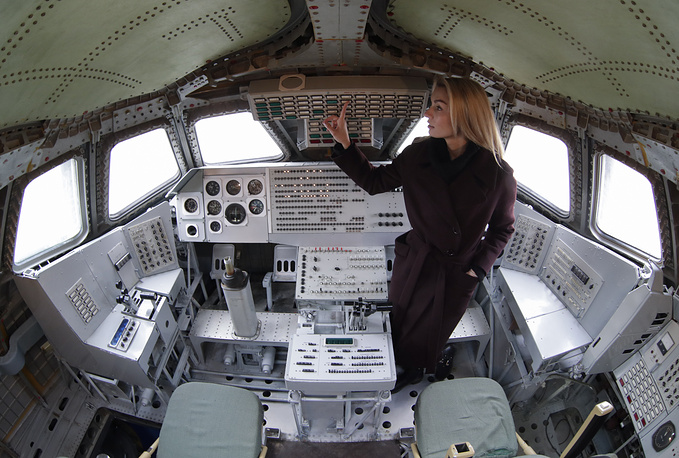 A woman in a cockpit of the model of Buran space shuttle installed at Baikonur cosmodrome museum
