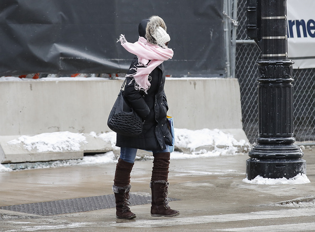 A woman braves the freezing weather as she crosses a street in Chicago