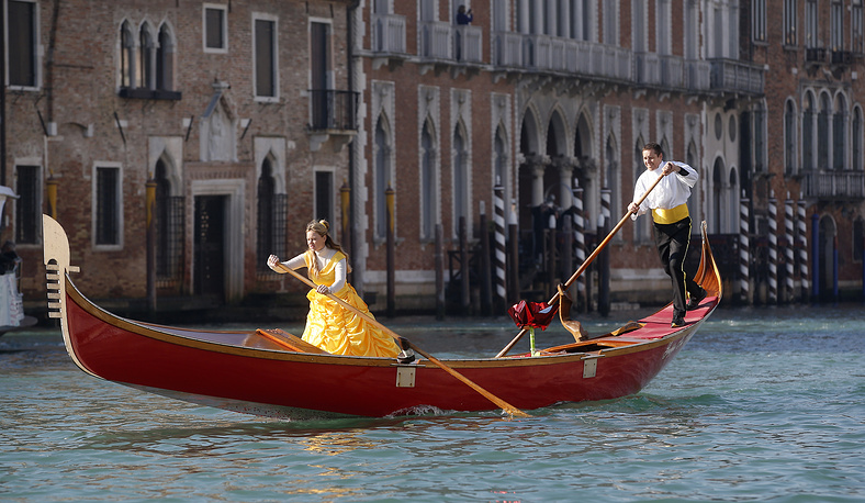 Masked people stand on a gondola during the water parade, part of the Venice Carnival