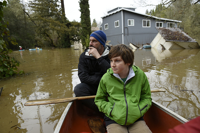 Local residents look at homes flooded by the Russian River from their canoe as they paddle through a neighborhood in Forestville