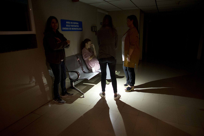Mothers and relatives wait outside of an intense care room for babies at a clinic, during a power outage in Caracas