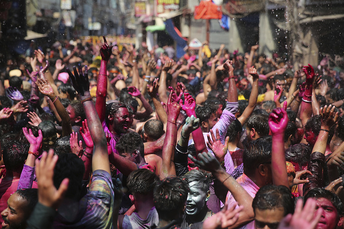 Indian revelers, faces smeared with colored powder, dance during celebrations to mark Holi in Allahabad