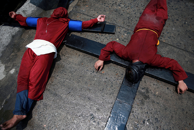 Filipino penitents bearing crosses on their backs lie on the street as they perform a ritual on Maundy Thursday in Mabalacat City, Philippines, April 18