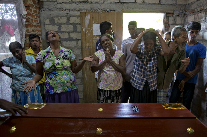 Relatives weeping near the coffin with the remains of 12-year Sneha Savindi, who was a victim of Easter Sunday bombing at St. Sebastian Church