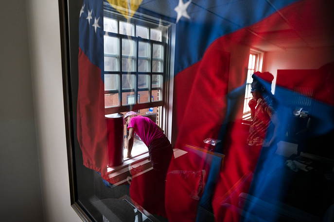 Activists Tighe Berry and Vonds August, who are against a forced handover of diplomatic buildings belonging to the Maduro government, prepare to hang a banner as they occupy the Venezuelan Embassy in Washington, April 24