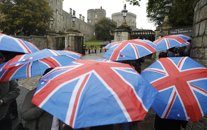 Tourists with British union flag umbrellas walking in the rain toward the entrance to Windsor Castle