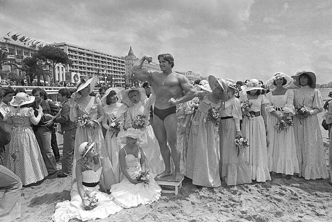 "Arnold Schwarzenegger showing off his body for an appreciative beach audience in Cannes, ahead of the presentation of his film ""Pumping Iron"" at the Cannes Film Festival , 1977"