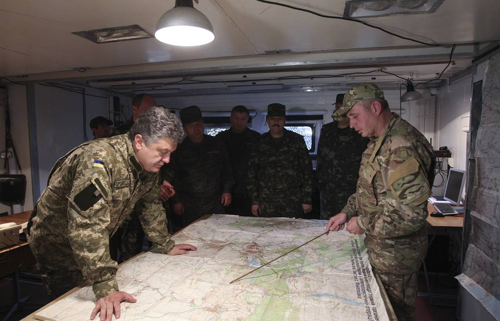 Ukrainian President Petro Poroshenko (left) listens to a report at a staff of the military operation in south east Ukraine EPA/MYKHAYLO MARKIV / PRESIDENTIAL PRESS SERVICE POOL