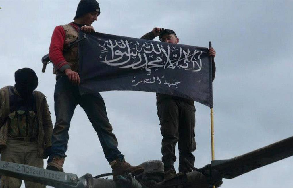 Rebels from Jabhat al-Nusra waving their flag AP Photo/Edlib News Network ENN, File