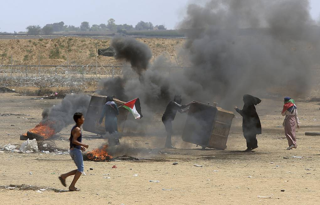 Palestinian protesters burn tires near the Israeli border fence, in the Gaza Strip AP Photo/Adel Hana