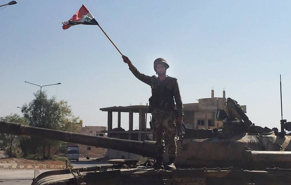 Syrian soldier standing on a tank in Khan Sheikhoun, Syria AP Photo/Albert Aji