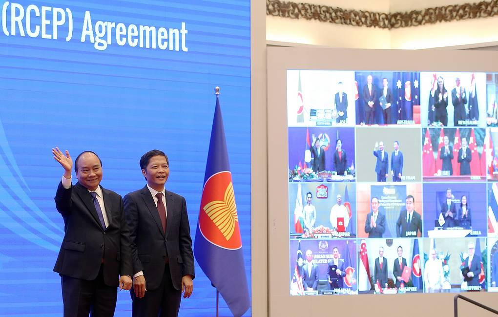 Vietnam's Prime Minister Nguyen Xuan Phuc and Minister of Industry and Trade Tran Tuan Anh cheering after the virtual signing ceremony for the Regional Comprehensive Economic Partnership (RCEP) in Hanoi EPA-EFE/LUONG THAI LINH