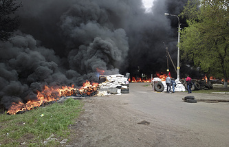Black smoke billows from burning tires at a checkpoint following an attack by Ukrainian troops outside Sloviansk
