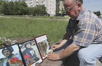 A local resident lights a candle in front of photos of Russian TV journalists, killed in Ukraine. On the photos are (L-R) Igor Kornelyuk, Anton Voloshin, both of Vesti 24, killed earlier this month, and Anatoly Klyan (Channel One) killed June 29