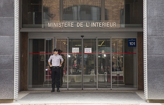 A police officer stands guard in front of the entrance of the Criminal Investigation Department of Nanterre, near Paris