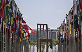 Broken Chair monument to land mine victims is seen among country flags at the Place des Nations in Geneva