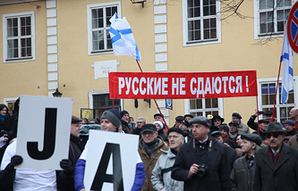 Protesters in Latvia hold a poster reading 'Russians don't give up'