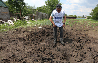 OSCE observer at a site of a shell crater in the village of Telmanovo