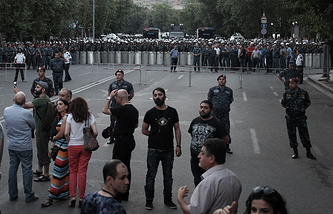 Demonstrators standing in front of police line during a protest rally in Yerevan